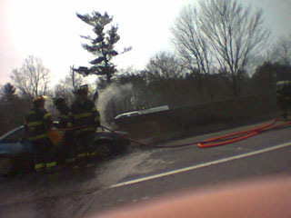 [Firemen surrounding a smoldering wreck of a car]